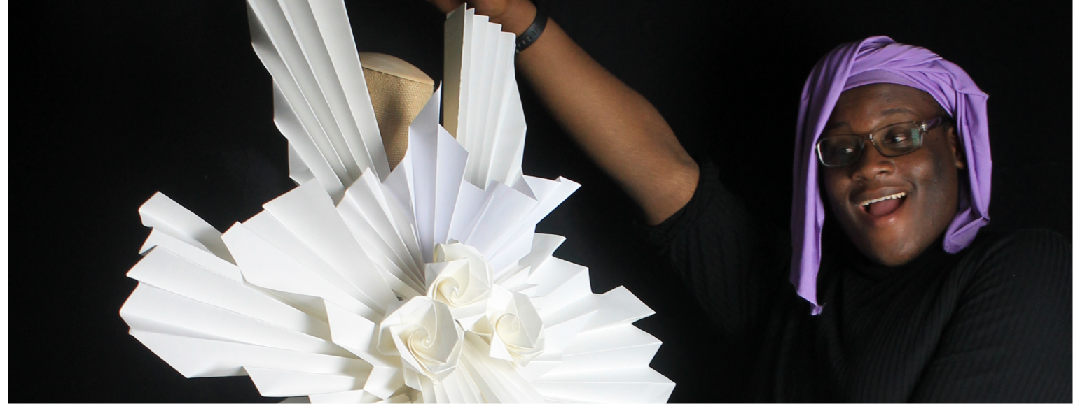 Photo of a student enthusiastically gesturing to a dress they made out of paper.