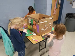 Kinder students working on a cardboard piece