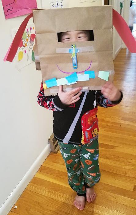 Kindergarten boy with a paper bag mask.