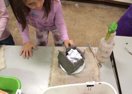 Elementary student work on a clay slab house.