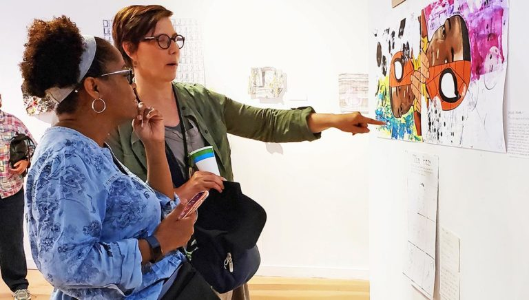 Two teachers looking at a work of art.